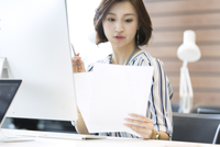 PCの前で資料を見るビジネス女性 33000004844| 写真素材・ストックフォト・画像・イラスト素材|アマナイメージズ