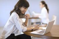 スマートフォンを持ちノートパソコンを見るビジネス女性 33000004927| 写真素材・ストックフォト・画像・イラスト素材|アマナイメージズ