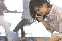 ノートパソコンを見てスマートフォンで通話するビジネス女性 33000004930| 写真素材・ストックフォト・画像・イラスト素材|アマナイメージズ