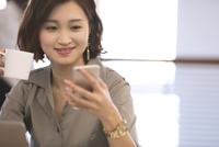 スマートフォンを見るビジネス女性 33000004932| 写真素材・ストックフォト・画像・イラスト素材|アマナイメージズ