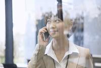スマートフォンで通話するビジネス女性 33000004941| 写真素材・ストックフォト・画像・イラスト素材|アマナイメージズ
