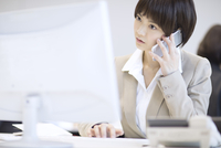 パソコンを見てスマートフォンで通話するビジネス女性 33000004944| 写真素材・ストックフォト・画像・イラスト素材|アマナイメージズ