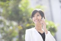 スマートフォンで通話するビジネス女性 33000004969| 写真素材・ストックフォト・画像・イラスト素材|アマナイメージズ