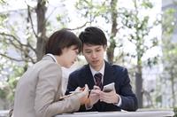 スマートフォンを見るビジネス男女 33000004975| 写真素材・ストックフォト・画像・イラスト素材|アマナイメージズ