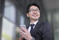 スマートフォンを持ち横を見るビジネス男性 33000004981| 写真素材・ストックフォト・画像・イラスト素材|アマナイメージズ