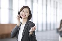 スマートフォンで通話するビジネス女性 33000004998| 写真素材・ストックフォト・画像・イラスト素材|アマナイメージズ