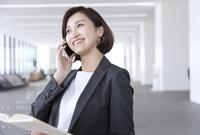 手帳を持ちスマートフォンで通話するビジネス女性 33000004999| 写真素材・ストックフォト・画像・イラスト素材|アマナイメージズ