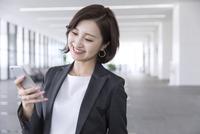 スマートフォンを操作するビジネス女性 33000005002| 写真素材・ストックフォト・画像・イラスト素材|アマナイメージズ