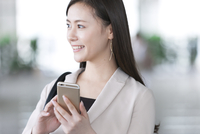 スマートフォンを持ち横を向くビジネス女性 33000005007| 写真素材・ストックフォト・画像・イラスト素材|アマナイメージズ