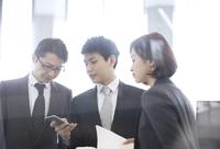スマートフォンを見て打ち合わせをする3人のビジネス男女 33000005037| 写真素材・ストックフォト・画像・イラスト素材|アマナイメージズ