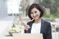 カメラ目線でスマートフォンを持つビジネス女性 33000005052| 写真素材・ストックフォト・画像・イラスト素材|アマナイメージズ