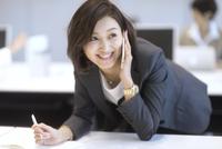 デスクに前のめりの体勢でスマートフォンで通話するビジネス女性 33000005063| 写真素材・ストックフォト・画像・イラスト素材|アマナイメージズ