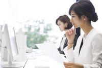 資料を持ちパソコンを見るビジネス女性 33000005065| 写真素材・ストックフォト・画像・イラスト素材|アマナイメージズ