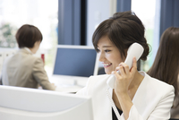 パソコンの前で電話をするビジネス女性 33000005066| 写真素材・ストックフォト・画像・イラスト素材|アマナイメージズ