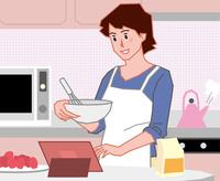 タブレットを見ながら料理をする若い女性