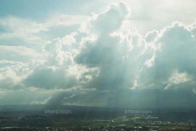 雲間から日差しさしこむ町の景観...