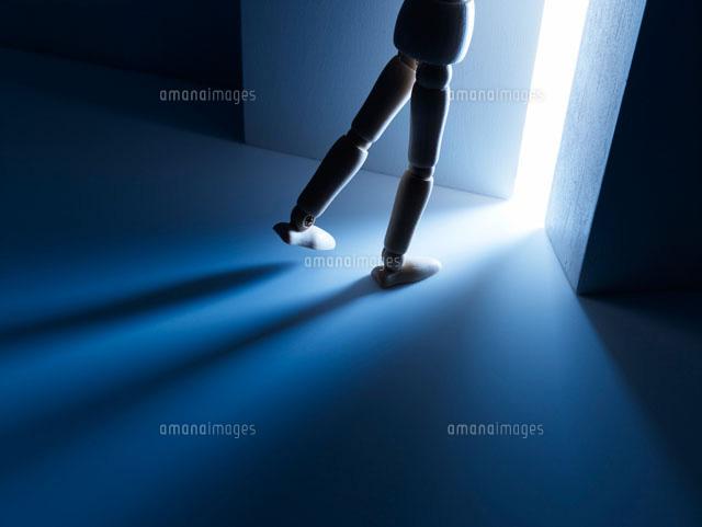 暗闇の中から扉を開けて光に向かう人形の足10132106041の写真素材