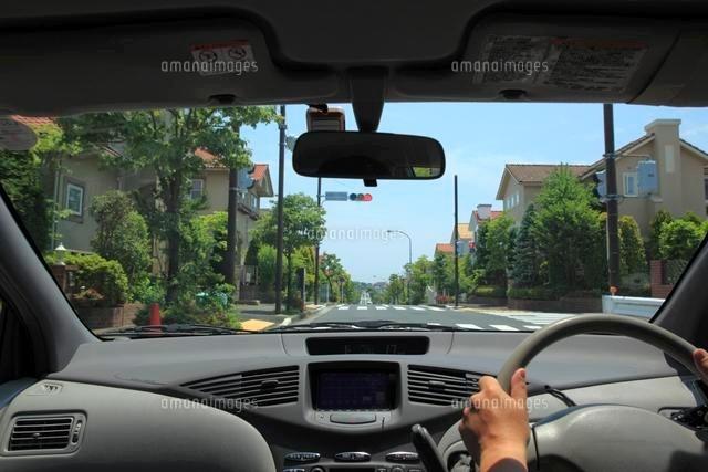 住宅街の赤信号で停車する車の運...