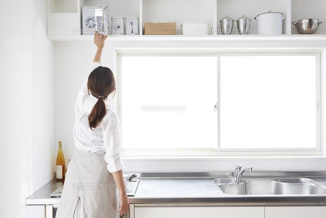 キッチンの戸棚から物を取る女性...