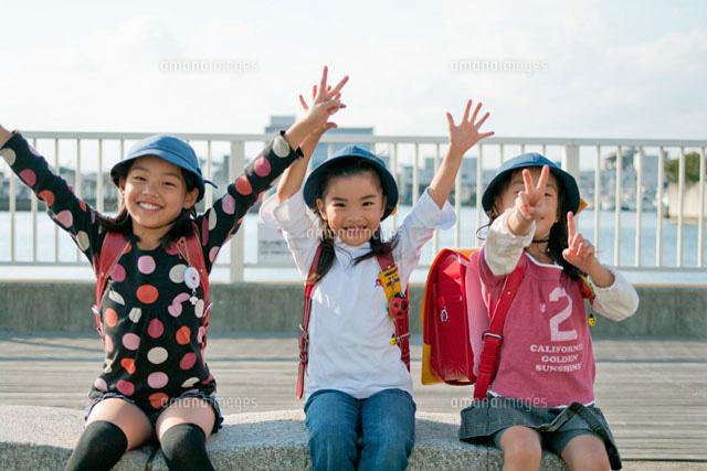 バンザイをする三人の小学生の女...