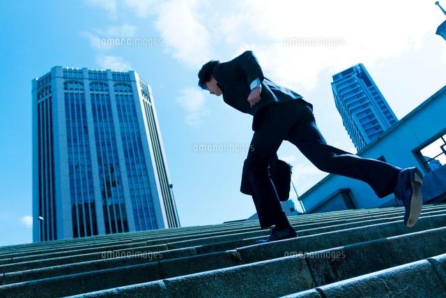 階段を駆け上る日本人ビジネスマ...