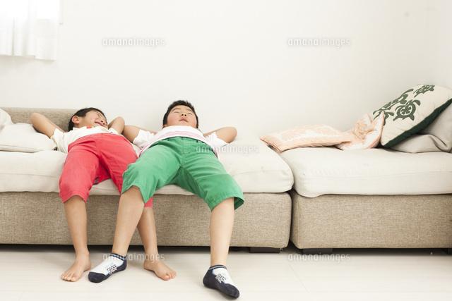 ソファーで寝転びながら遊び笑う小学生の兄弟[10337000821]の写真 ...