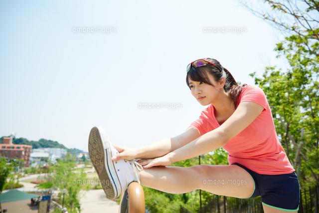 運動前に準備運動をする若い女性...