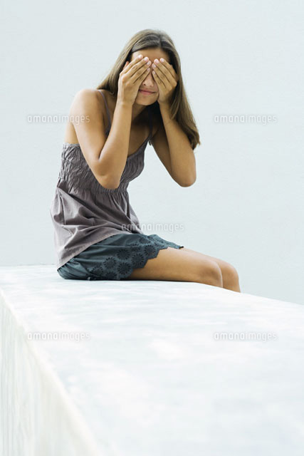 girl sitting, covering eyes with hands