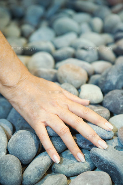 Woman touching pebbles of hand