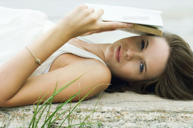 girl lying and holding book over face