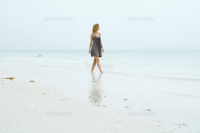 Woman in sundress walking along beach
