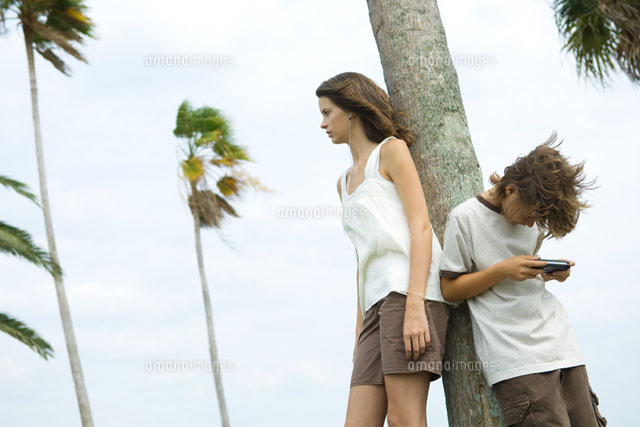 Siblings leaning against tree trunk