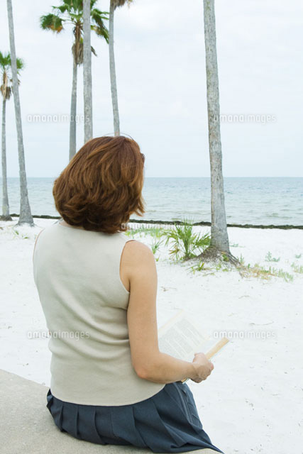 Woman reading book at the beach