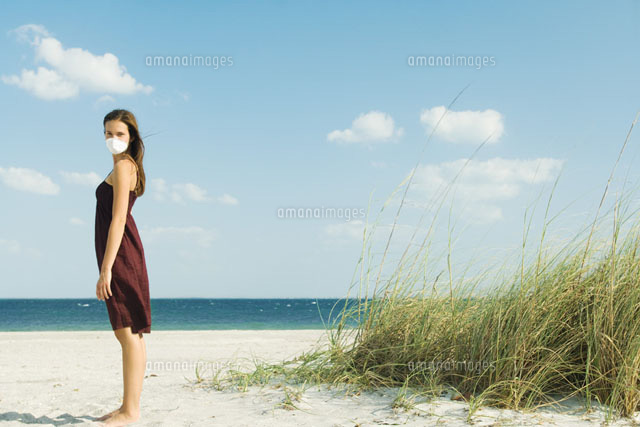 Woman standing & wearing pollution mask