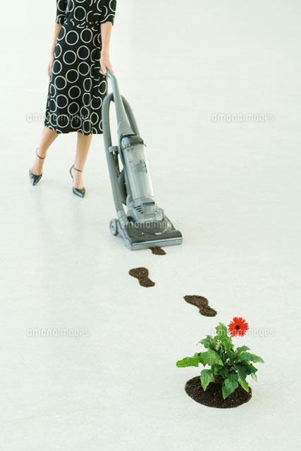 Woman vacuuming up footprints of soil