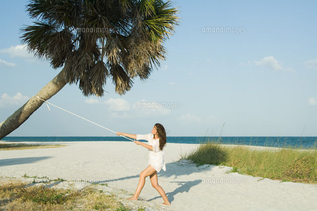 Woman pulling palm tree with rope