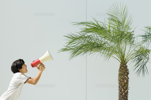 Boy yelling at palm tree with megaphone