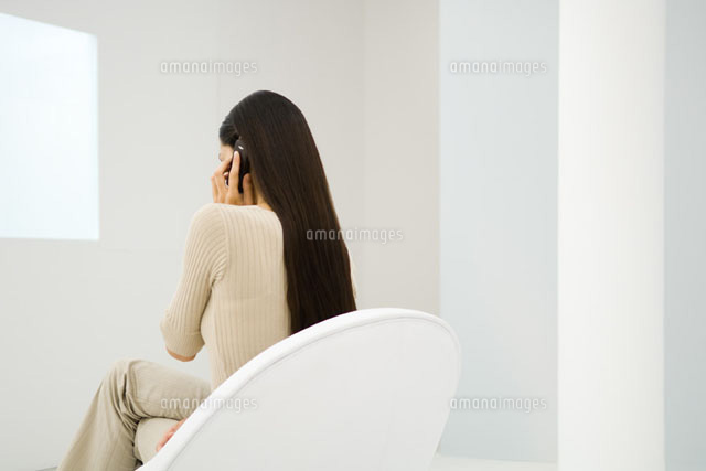 Woman sitting in chair, using cell phone