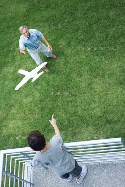 Boy throwing toy airplane to grandfather