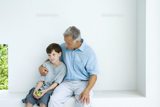 Man sitting with arm around grandson