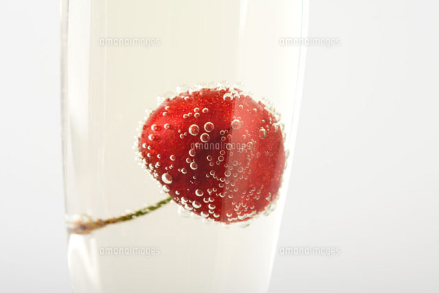 Cherry floating in glass of champagne, close-up