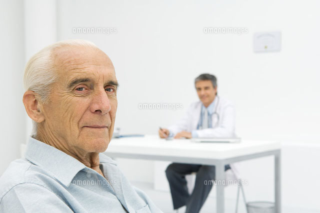 Doctor working at desk, focus on senior patient
