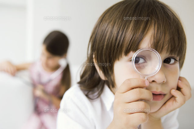 Little boy looking through magnifying glass at camera