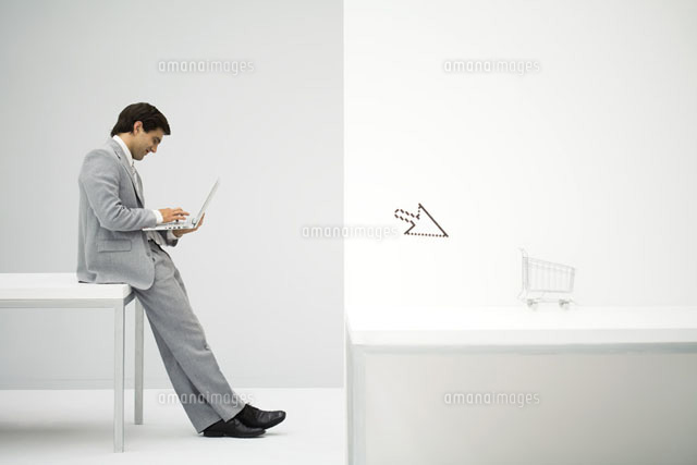 Businessman sitting on desk, shopping online