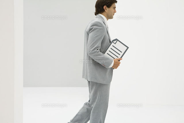 Businessman walking, carrying document, side view