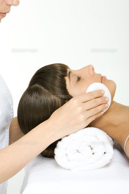 Woman having her make-up removed, using towel as a pillow