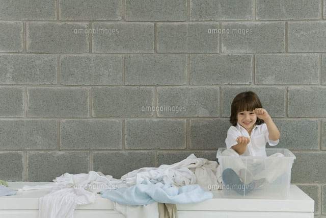 Little boy sitting in plastic storage container