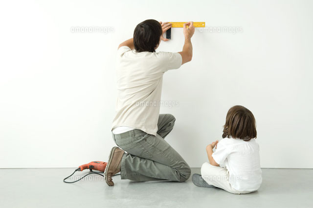 Man measuring wall with a ruler while his son watches