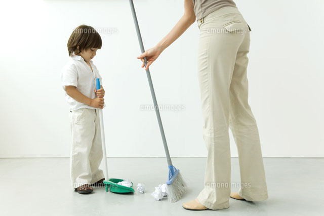Little boy helping his mother sweep the floor
