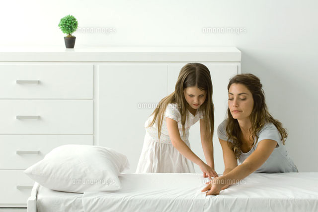 Mother and daughter making bed together